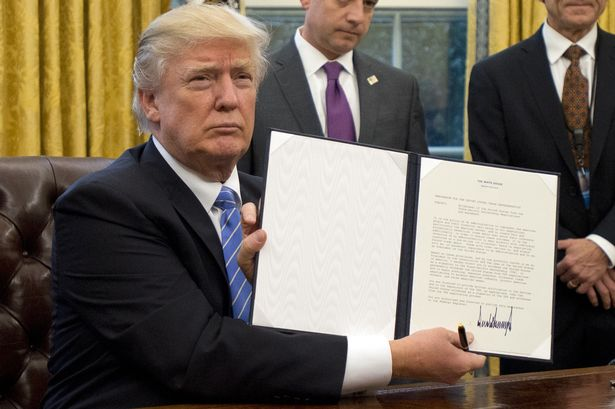 President Donald Trump signing an executive order freezing hiring for federal positions.